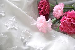Artificial Pink Carnation on White Fabric Stock Photography