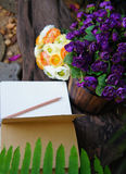Artificial purple and yellow roses with an open note book Royalty Free Stock Image