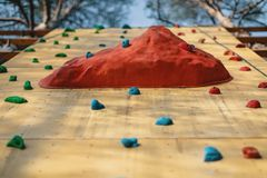 Artificial rock climbing wall at outdoor gym adventure park royalty free stock image