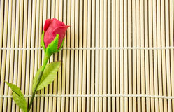 Artificial rose on bamboo background. Red artificial rose on bamboo background Royalty Free Stock Image