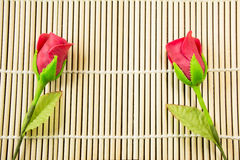 Artificial rose on bamboo background. Two artificial roses on bamboo background Stock Image