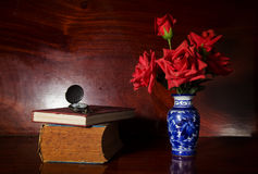 Artificial rose in vase with watch and book. Stock Photography