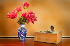 Artificial rose in vase with watch and book. Royalty Free Stock Photo
