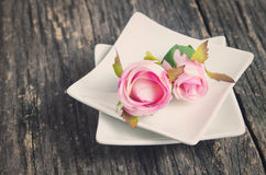 Artificial rose in white plate Stock Photography