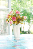 Artificial roses in ceramic vase near window Royalty Free Stock Photos