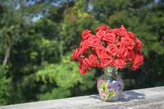 Artificial Roses in Clear Glass Vase on Concrete Surface Stock Photo