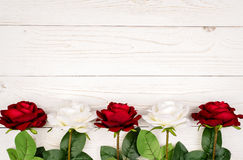 Artificial roses on the wooden background. Artificial white and red roses on the wooden background Stock Photography