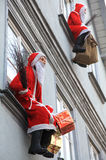 Artificial Santa Claus on house facade. Two artificial Santa Clauses sitting on window sills Stock Images