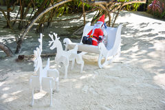 Artificial Santa Clause with deers riding on the beach Royalty Free Stock Photo