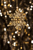 Artificial Snowflake in gold on glitter background Stock Photos