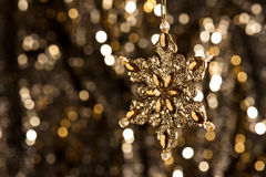 Artificial Snowflake in gold on glitter background Stock Image