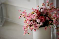 Artificial spray roses pink pastel colors are in a white vase. Artificial spray roses pink pastel colors in a white vase Royalty Free Stock Photo