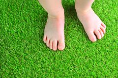 Artificial turf background. Tender foots of a baby on a green artificial grass floor. stock photos
