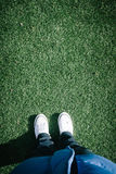 Artificial turf grass on sports field with two shoes, personal p Royalty Free Stock Photography