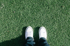 Artificial turf grass on sports field with two shoes, personal p Royalty Free Stock Photo