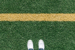 Artificial turf grass on sports field with two shoes, personal p Stock Image
