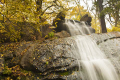 Artificial waterfall in autumn park. Waterfall in autumn park covered with golden leaves Royalty Free Stock Photo