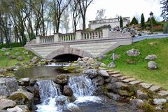 An artificial waterfall in a city park. In early spring Stock Photos