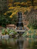 Artificial waterfall Lithia Park in the Autum. Ashland, Oregon, USA, long exposure, featuring yellow and red leaves royalty free stock photography