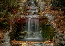 Artificial waterfall Lithia Park in the Autum. Close-up on artificial waterfall Lithia Park in the Autum, Ashland, Oregon, USA, long exposure, featuring yellow stock images