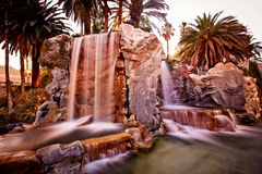 Artificial waterfall with palm trees Stock Photography