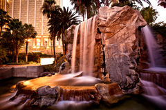 Artificial waterfall with palm trees Stock Photo