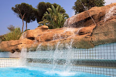 Artificial waterfall in the pool. Royalty Free Stock Image