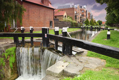 Artificial waterfall and river. small houses Stock Photos