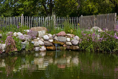 Artificial waterfall. Willow fences and trees in the background, willow fences and trees in the background Stock Photos