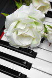 Artificial white rose on piano Royalty Free Stock Image