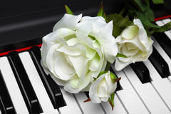 Artificial white rose on piano Stock Images