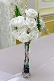 Artificial white roses in a vase. Artificial white roses and fern in a vase decorate an interior Stock Images