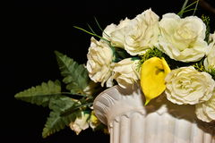 Artificial white roses in a vase and plastic boxes at night Stock Photography