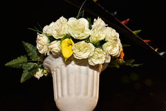 Artificial white roses in a vase and plastic boxes in the sky at night Royalty Free Stock Photos