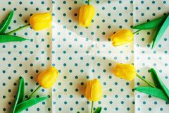 Artificial yellow tulips on blue polka dot fabric or tablecloth stock image