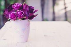 Artificiel pourpre s'est levé dans la tasse pour l'amour Photographie stock