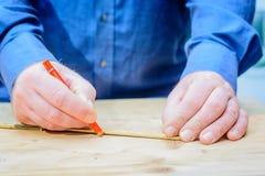 Artigiani che misurano con il righello, camicia blu d'uso fotografia stock