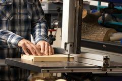 Artigiano che per mezzo della lama a nastro per tagliare un pezzo di legno per graduare fotografia stock