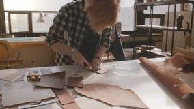 Artigiano maschio che cammina nell'officina fabbricante, craftswoman che taglia cuoio in pezzi per il movimento lento fatto a man