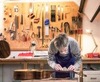 Artigiano nella sua officina che livella i cerchi di una chitarra Immagini Stock Libere da Diritti