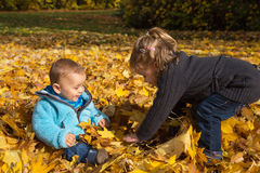 Artigo do outono: irmão e irmã que têm o divertimento no outono que joga a sagacidade Fotos de Stock