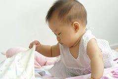 Artigo encontrando infantil asiático sob uma cobertura imagens de stock royalty free