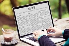 Artigo noticioso da leitura da mulher no portátil/tela de computador imagem de stock royalty free