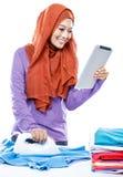 Artigo vestindo da leitura do hijab da jovem mulher na tabuleta quando ironin fotos de stock royalty free