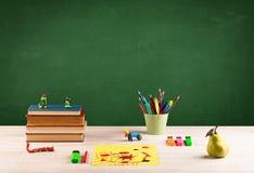 Artigos da escola na mesa com quadro vazio Fotografia de Stock