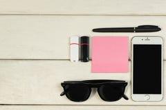 Artigos de papelaria, óculos de sol, telefone, cartões de memória Flash em uma tabela de madeira fotos de stock