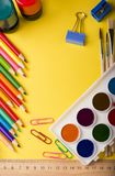 Artigos de papelaria coloridos da escola no fundo amarelo fotografia de stock royalty free
