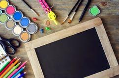 Artigos de papelaria com placa de giz, de volta ao espaço b da cópia do conceito da escola Fotos de Stock