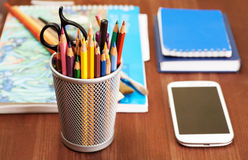 Artigos de papelaria diferentes no suporte na tabela de madeira Fotografia de Stock Royalty Free