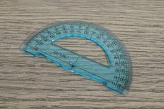 Artigos de papelaria, goniômetro azul em uma tabela de madeira imagem de stock